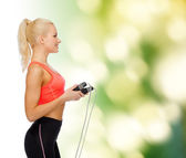 Smiling sporty woman with skipping rope — Stock Photo