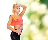 Tired sporty woman with towel and water bottle — Stock Photo