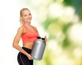 Smiling sporty woman with jar of protein — Stock Photo