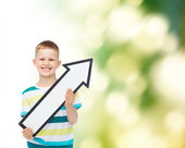 Smiling little boy with blank arrow pointing right — Stock Photo