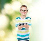 Smiling boy in eyeglasses holding spectacles — Stock Photo