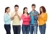 Group of serious teenagers with smartphones — Stock Photo