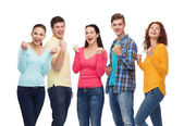 Group of smiling teenagers showing triumph gesture — Stock Photo