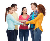 Smiling teenagers with hands on top of each other — Stock Photo