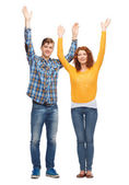 Smiling teenagers with raised hands — Stock Photo