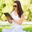 Smiling young girl with tablet pc sitting on grass — Stock Photo #51195161