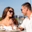Smiling couple eating dessert at cafe — Stock Photo #51197463