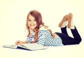 Smiling little student girl lying on the floor — Stock Photo