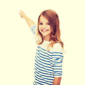 Smiling girl pointing at virtual screen — Stock Photo