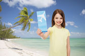 Smiling little girl with airplane ticket — Stockfoto