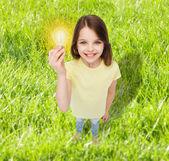 Smiling little girl holding light bulb — Stock Photo