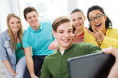 Smiling students making selfie with tablet pc — Stock Photo
