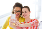Girlfriends taking selfie with smartphone camera — Stock Photo