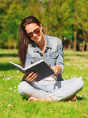 Smiling young girl with book sitting in park — Stock Photo