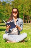 Sorridente giovane ragazza con libro seduto nel parco — Foto Stock
