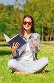 年轻的女孩微笑着本书坐在草地上 — 图库照片