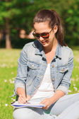 Smiling young girl with notebook writing in park — Stockfoto