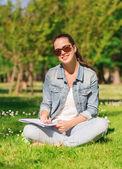 Sourire de jeune fille avec cahier d'écriture dans le parc — Photo