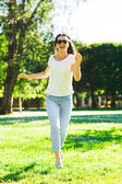 Smiling young woman with sunglasses in park — Stock Photo