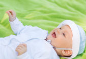 Smiling baby lying on floor and looking up — Stock Photo