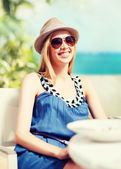 Girl in shades in cafe on the beach — Stock Photo