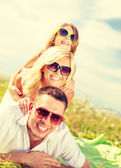 Smiling family in sunglasses lying on blanket — Стоковое фото