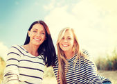 Smiling girlfriends having fun on the beach — Stock Photo