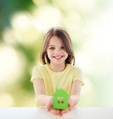 Beautiful little girl holding paper house cutout — Stock Photo