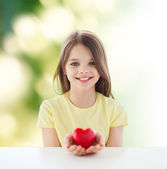 Beautiful little girl sitting at table — Stock Photo