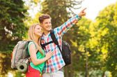 Smiling couple with backpacks in nature — Stock Photo