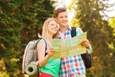 Smiling couple with map and backpack in forest — Stock Photo
