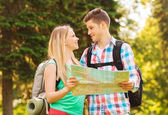 Smiling couple with map and backpacks in forest — Stock Photo
