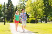 Smiling couple walking in park — Stockfoto