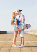 Smiling couple with skateboard kissing outdoors — Stock Photo