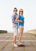 Smiling couple with skateboard outdoors — Stock Photo
