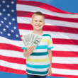 Smiling boy holding dollar cash money in his hand — Stock Photo