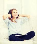 Chica con tablet pc y auriculares en casa — Foto de Stock