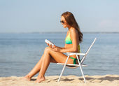 Smiling young woman sunbathing in lounge on beach — Stock Photo