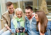 Group of smiling friends with digital photocamera — Stock Photo