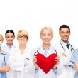Smiling doctors and nurses with red heart — Stock Photo #51349325