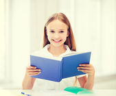 Girl studying and reading book at school — Stock Photo
