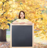 Happy little girl with blank blackboard — Stock Photo