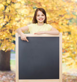 Happy little girl pointing finger to blackboard — Stock Photo