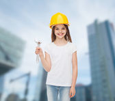 Smiling little girl in hardhat with wrench — Stok fotoğraf