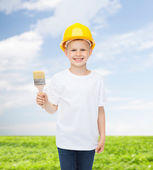 Smiling little boy in helmet with paint brush — Stock Photo