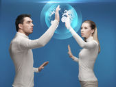 Man and woman working with globe hologram — Foto de Stock