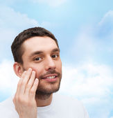 Beautiful smiling man touching his face — Stock Photo