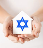 Hands holding house with star of david — Stock Photo
