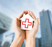 Hands holding paper house with red cross — Stockfoto