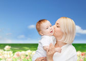Happy mother kissing smiling baby — Стоковое фото